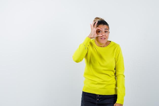 Giovane donna che mostra segno ok sull'occhio in maglione giallo e pantaloni neri e sembra felice looking