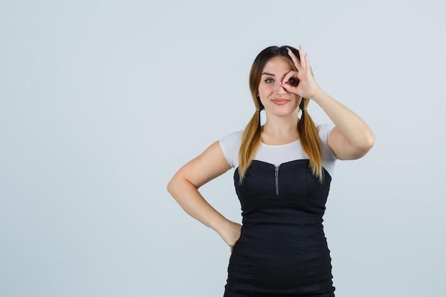 Giovane donna che mostra segno ok sull'occhio