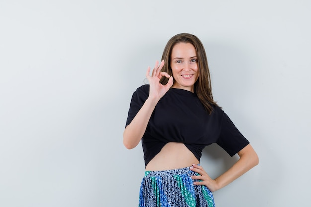 Young woman showing ok sign and holding one hand on waist in black t-shirt and blue skirt and looking happy