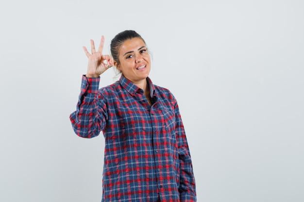 チェックのシャツでokサインを示し、きれいに見える若い女性。正面図。