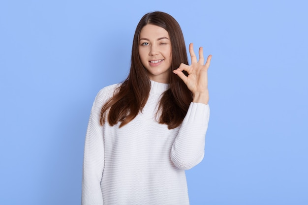 Young woman showing ok sign isolated over blue wall