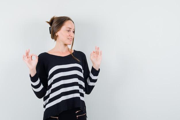 Молодая женщина показывает знак ок обеими руками в полосатом трикотажном белье и черных брюках и выглядит счастливой