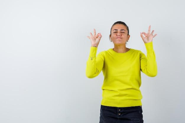 Молодая женщина показывает хорошие знаки, закрывает глаза в желтом свитере и черных брюках и выглядит спокойной