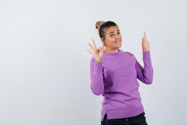 Giovane donna che mostra segni ok