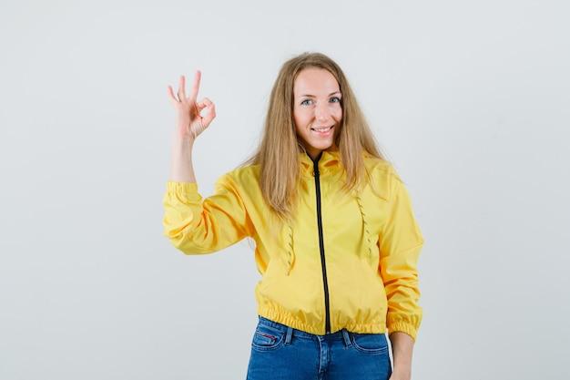 괜찮아 기호를 표시하고 노란색 폭격기 재킷과 블루 진에 침묵 제스처를 보여주는 젊은 여자와 심각한, 전면보기를 찾고.