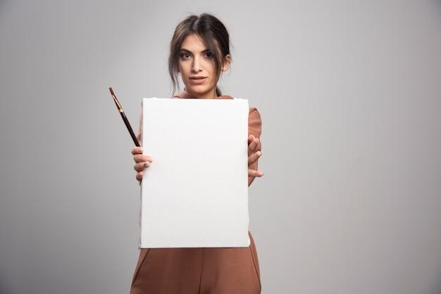 Giovane donna che mostra i pennelli e la tela