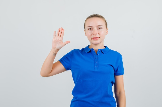 Young woman showing palm in blue t-shirt and looking confident