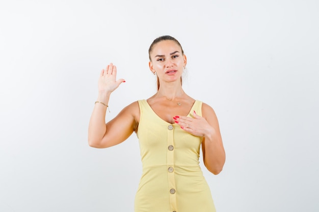 Молодая женщина показывает ладонь, держа руку на груди в желтом платье и выглядит уверенно, вид спереди.