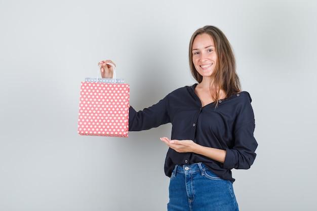 黒のシャツ、ジーンズのショートパンツと陽気に見える紙袋を示す若い女性