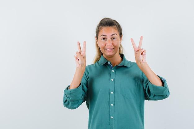 緑のブラウスに笑みを浮かべて、かわいく見える間、平和のジェスチャーを示す若い女性