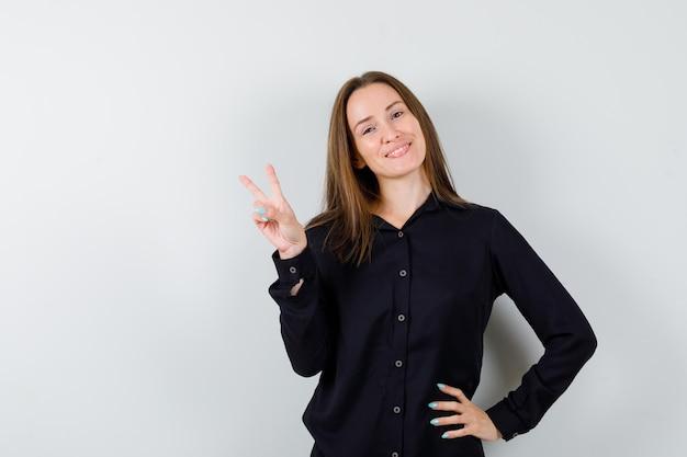 Giovane donna che mostra gesto di pace