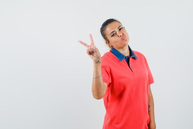 Молодая женщина показывает знак мира, изгибая губы в красной футболке и выглядит красиво, вид спереди.
