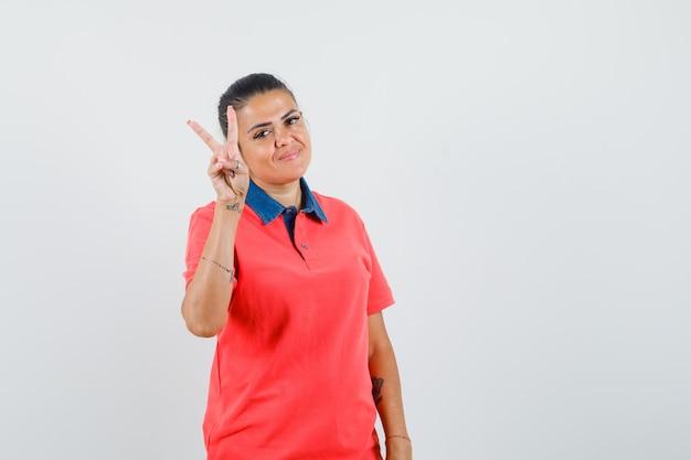 Молодая женщина показывает знак мира в красной футболке и выглядит довольно, вид спереди.