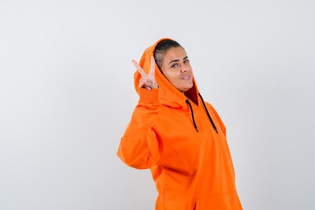 Giovane donna che mostra segno di pace in felpa con cappuccio arancione e sembra felice