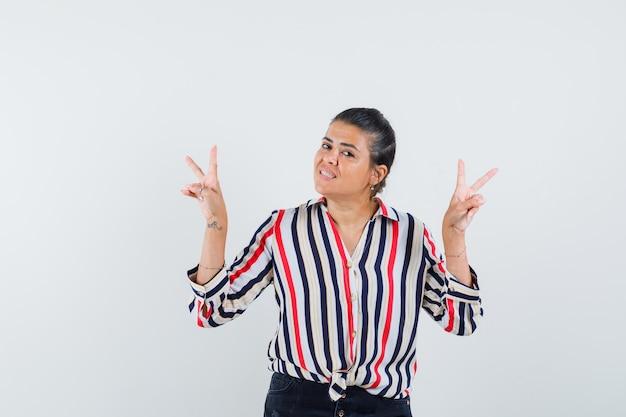 Giovane donna che mostra segni di pace con entrambe le mani in camicetta a righe e sembra ottimista