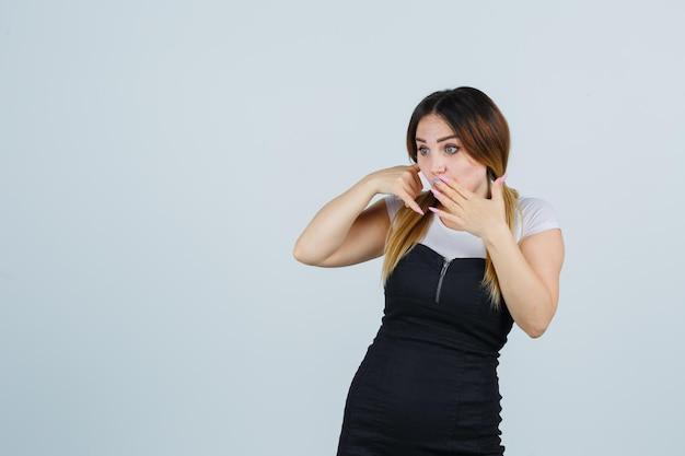 電話のジェスチャーを示し、驚いて見える若い女性
