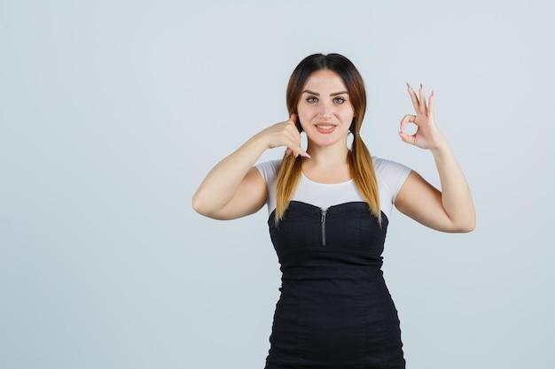 Молодая женщина показывает жест телефона и знак ок