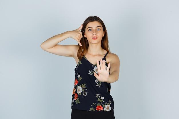 電話のジェスチャーを示し、ブラウスのサインインを停止し、真剣に見える若い女性。正面図。