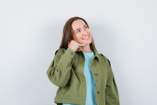 Молодая женщина показывает жест телефона, глядя вверх в футболке, куртке и выглядит весело. передний план.
