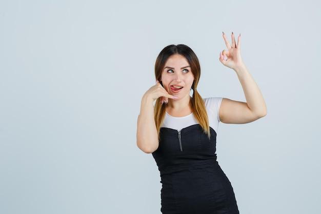 Giovane donna che mostra il gesto del telefono e il segno ok mentre tira fuori la lingua