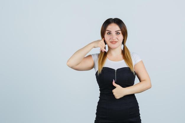 Giovane donna che mostra il gesto del telefono e il pollice in alto