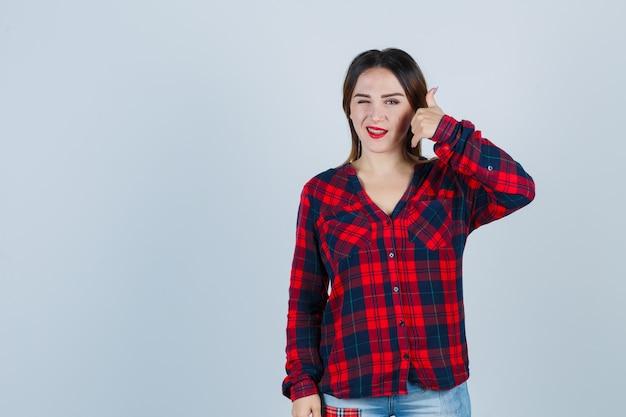 Giovane donna che mostra il gesto del telefono mentre sbatte le palpebre in camicia a quadri e sembra sicura, vista frontale.