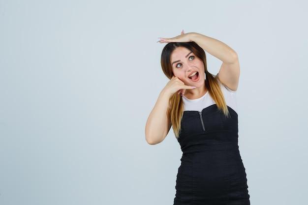 Giovane donna che mostra il gesto del telefono mentre tiene la mano sulla testa