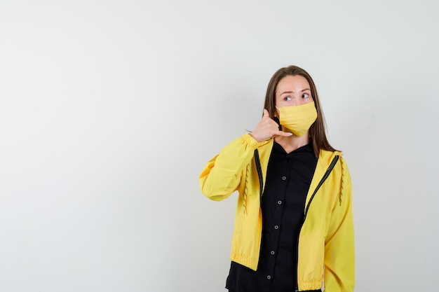 Young woman showing phone gesture