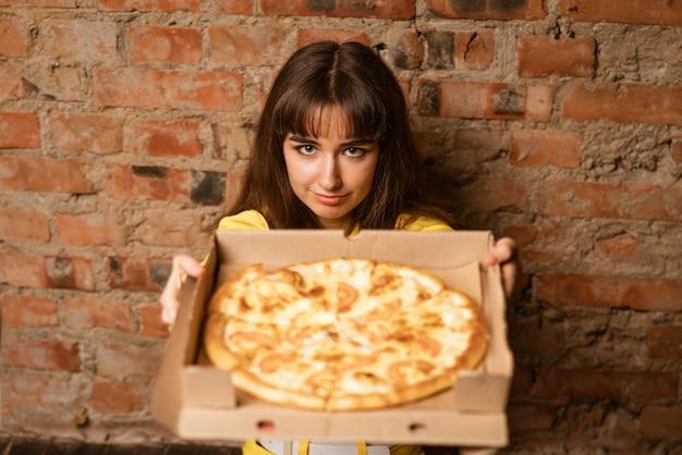 상자에 피자를 보여주는 젊은 여자를 닫습니다.