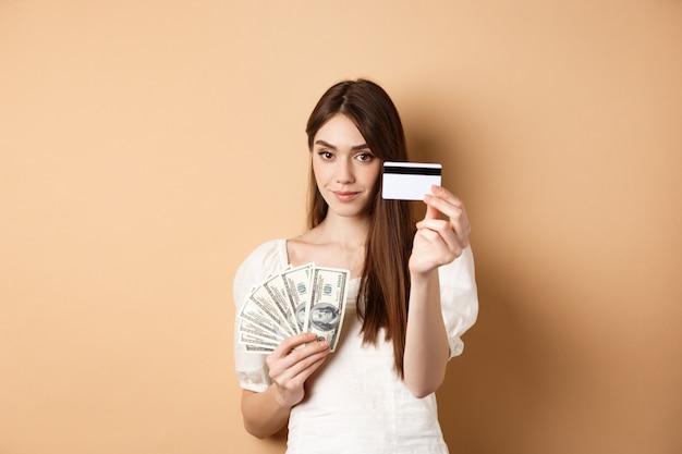 プラスチック製のクレジットカードを見せている若い女性は、ベージュの背景に立って、ドル札よりも非接触型決済を好みます。