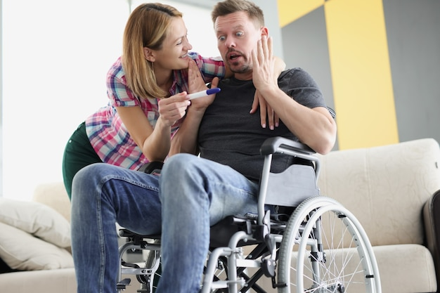 Young woman showing positive pregnancy test to disabled man in wheelchair