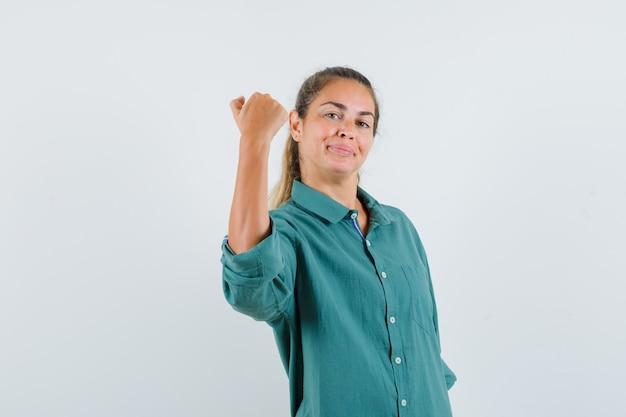 Giovane donna che mostra il gesto di potere in camicetta verde e sembra sicura