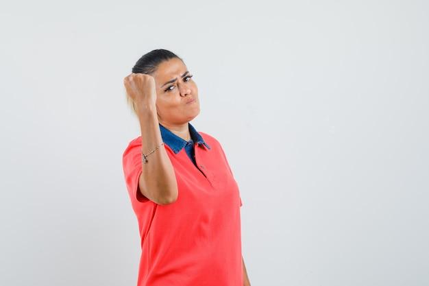 Giovane donna che mostra il gesto di potere in maglietta rossa e che sembra sicura. vista frontale.