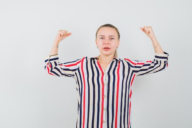 Giovane donna che mostra il gesto di potere in camicetta a righe e che sembra sicura