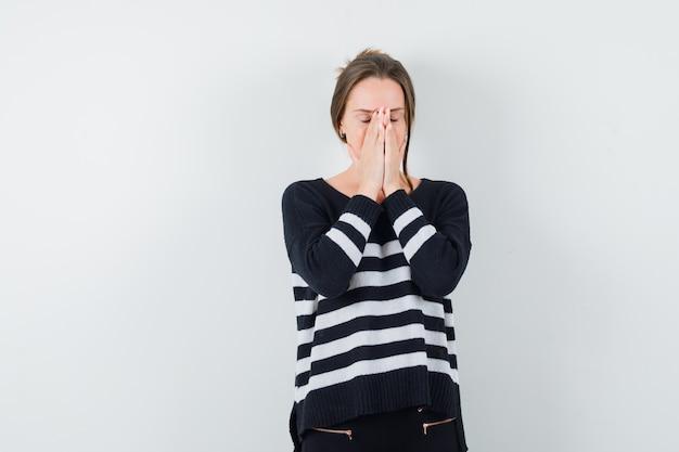 Молодая женщина показывает молитвенный жест в полосатом трикотажном белье и черных брюках и смотрит сосредоточенно