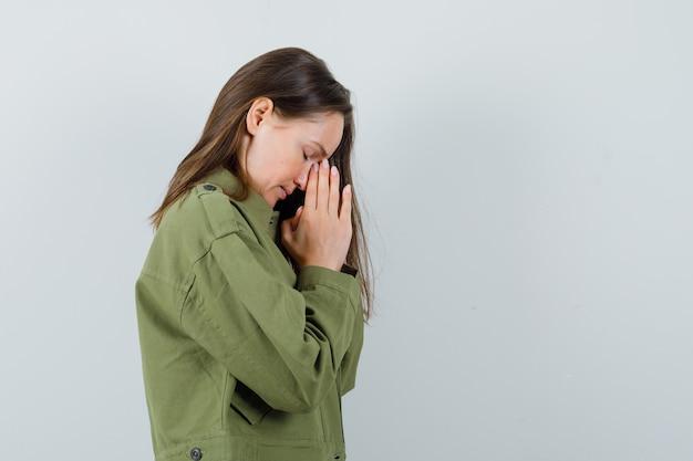 녹색 재킷에기도 제스처를 보여주는 젊은 여자와 희망을 찾고. .