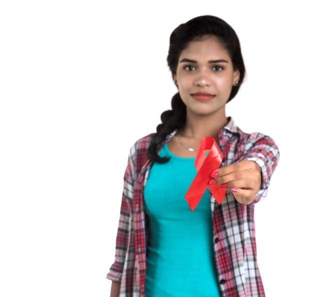 赤いリボンhiv、エイズ意識リボン、ヘルスケアと医学の概念を示す若い女性