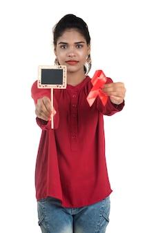 Молодая женщина показывает красную ленту вич, ленту осведомленности о спиде, понятие здравоохранения и медицины