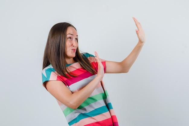 Молодая женщина показывает жест отказа в футболке и выглядит испуганной, вид спереди.