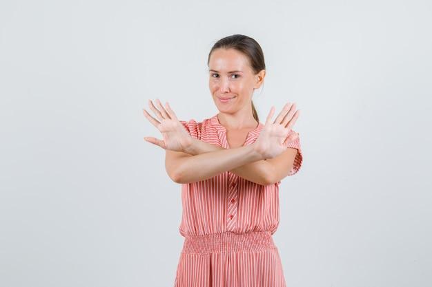 Giovane donna che mostra il gesto di rifiuto e sorridente in abito a righe, vista frontale.