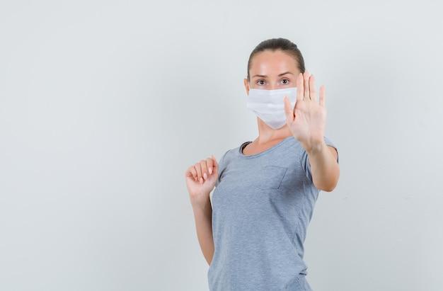Giovane donna che mostra il gesto di rifiuto in t-shirt, maschera e che sembra serio, vista frontale.