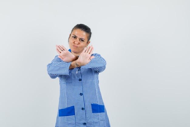 Giovane donna che mostra il gesto di restrizione in camicia del pigiama a quadretti blu e sembra arrabbiata. vista frontale.