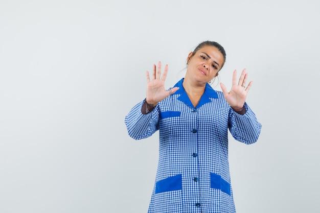 Giovane donna che mostra il gesto di restrizione in camicia del pigiama a quadretti blu e sembra carina. vista frontale.
