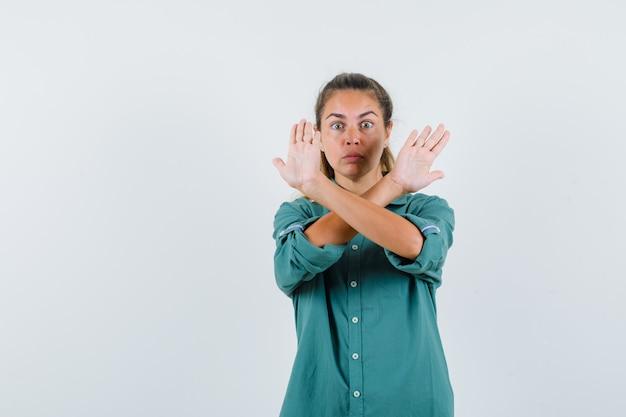 Молодая женщина показывает ограничение или жест x в зеленой блузке и выглядит серьезно