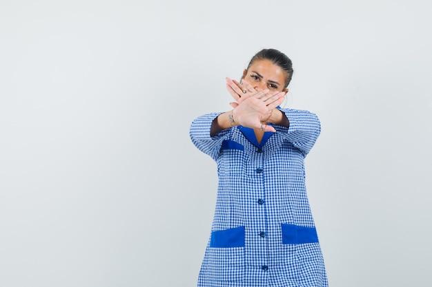Giovane donna che mostra il segno di restrizione in camicia del pigiama a quadretti blu e che sembra seria. vista frontale.