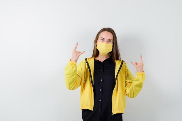 Молодая женщина, показывающая жест рок-н-ролла