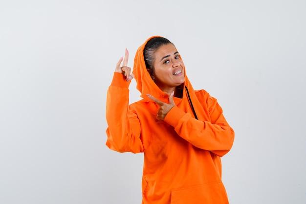 Молодая женщина показывает жест рок-н-ролла и указывает на него в оранжевой толстовке с капюшоном и выглядит красивой