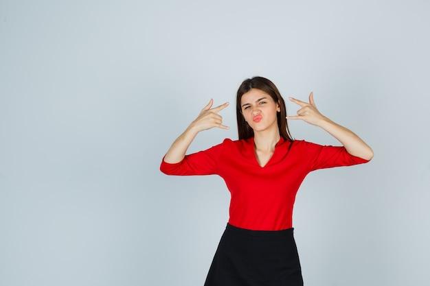 Молодая женщина демонстрирует рок-н-ролльный жест в красной блузке, черной юбке и выглядит уверенно