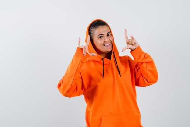 Giovane donna che mostra gesti rock n roll in felpa con cappuccio arancione e sembra bellissima