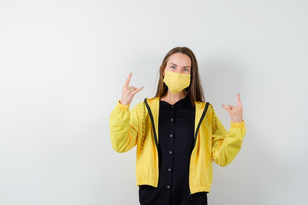 Young woman showing rock and roll gesture